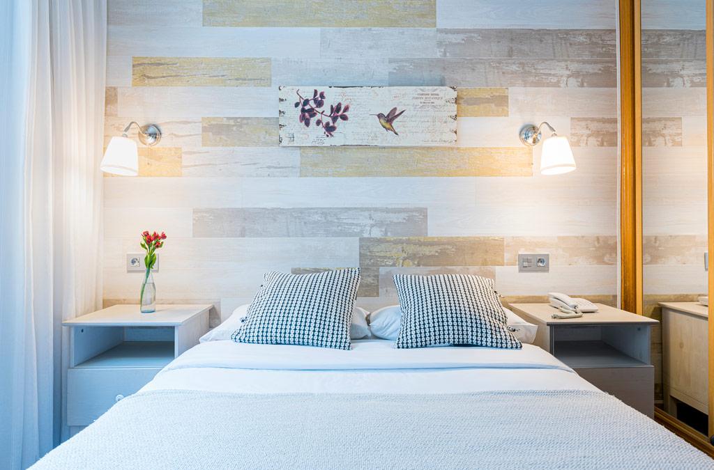 Habitación con cama matrinominal decorada en colores suaves y confortables