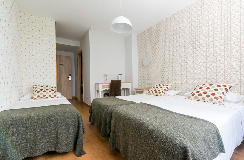 Habitación triple decorada en tonos neutros en Hotel Costa Verde